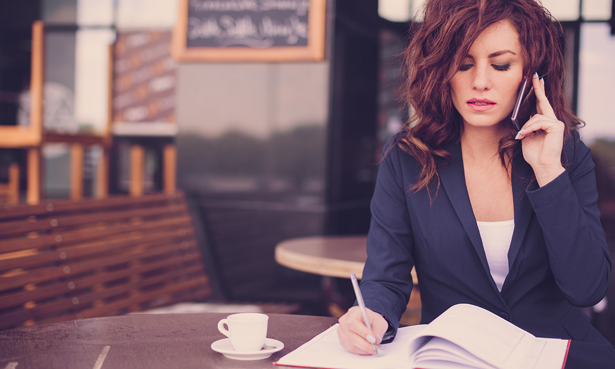 Young-business-woman-sitting-at-the-table-writing-in-a-notebook-and-talking-on-the-phone